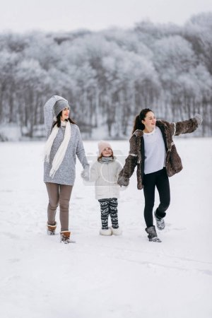 Side view of family running on snow on winter park background