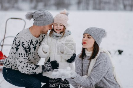 Perents sitting down with daughter and playing with snow