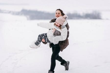 Elder sister holding smaller sister in hands and having fun in winter park