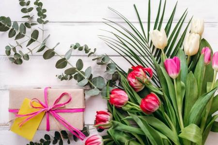 Composition of gift box with note and tulip bouquet on wooden planks background