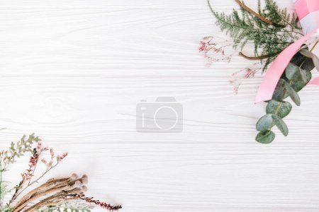 Floral bouquets with white gift box on white wooden background