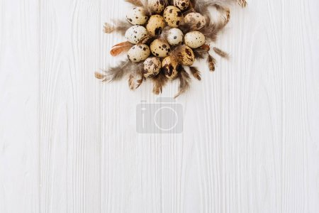 Composition with pile on top of quail eggs and feathers on white wooden background