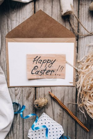 Top view of envelope, letter with Happy Easter lettering, pencil, nest, quail eggs, gift box with ribbon, cloth and threads on wooden planks background