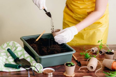 Cropped view of female hands in white gloves fillind empty pot with soil on background with gardening tools