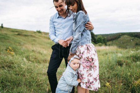 Husband hugging wife and small daughter standing near on meadow