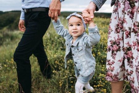 Photo for Cropped view of sad little girl holding hands with parents and walking by field - Royalty Free Image