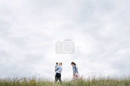 Photo pour Vue du dessous de la famille marche sur Prairie sur fond de ciel nuageux - image libre de droit