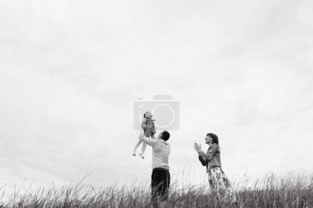 Photo pour Vue du dessous de la famille, jouer et s'amuser sur Prairie sur fond de ciel nuageux - image libre de droit