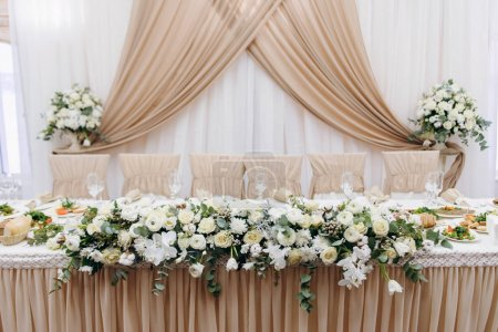 Wedding table with festive floral decoration, peach cloth, chair covers and curtains