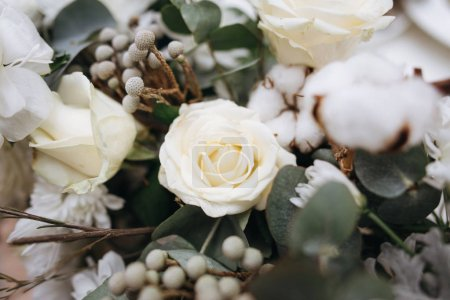 Floral composition with white roses, white flowers, buds, green leaves and decorative plants with blurred background