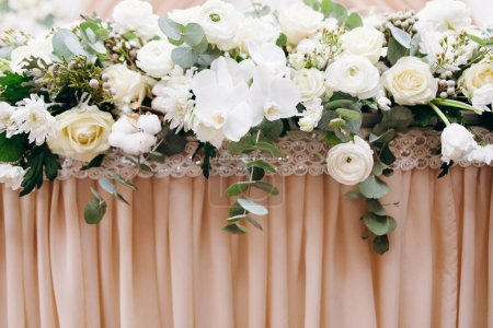Photo for Cropped view of wedding table decorated with peach cloth and festive floral composition - Royalty Free Image