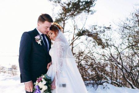 Photo pour Les nouveaux mariés romantiques hugging dehors en journée d'hiver - image libre de droit