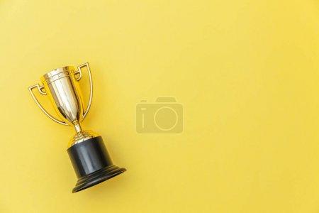 Photo pour Le vainqueur du design plat ou le vainqueur du trophée d'or est isolé sur fond jaune coloré. Victoire au premier rang de la compétition. Concept gagnant ou succès. Espace de reproduction en haut - image libre de droit