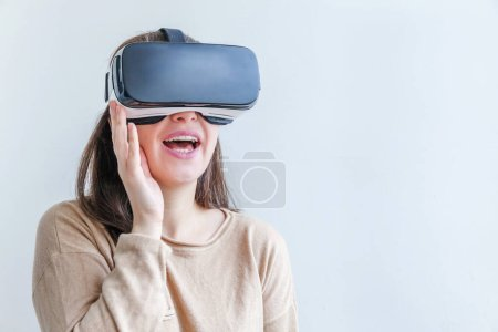 Photo for Smile young woman wearing using virtual reality VR glasses helmet headset on white background. Smartphone using with virtual reality goggles. Technology, simulation, hi-tech, videogame concept - Royalty Free Image