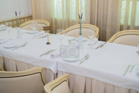 Photo for Forks, knives and glasses on the table in a modern restaurant - Royalty Free Image