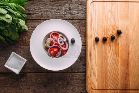 Preparing a Greek salad in a white dish on a wooden background w
