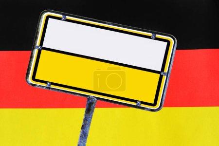 Photo pour Panneau routier vide devant un drapeau allemand. Plaque vide d'Allemagne - image libre de droit
