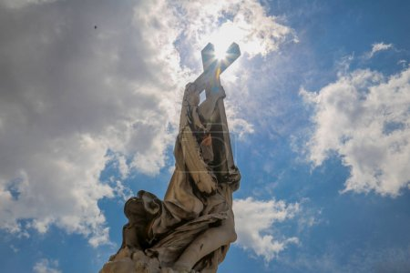 Statue of Jesus Christ with Cross against cloudy sky