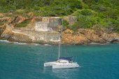 A catamaran sailing by Prince Frederikas Battery. Fort Willoughby on Hassel Island, St Thomas U.S. Virgin Islands.