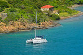 A catamaran sailing by Garrison house at Fort Willoughby on Hassel Island, St Thomas U.S. Virgin Islands.