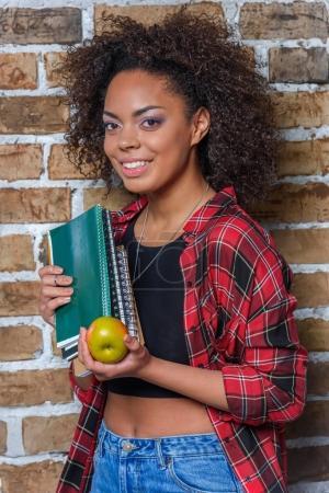 Photo pour Afro-américaine fille tenant pomme et cahiers tout en regardant la caméra - image libre de droit