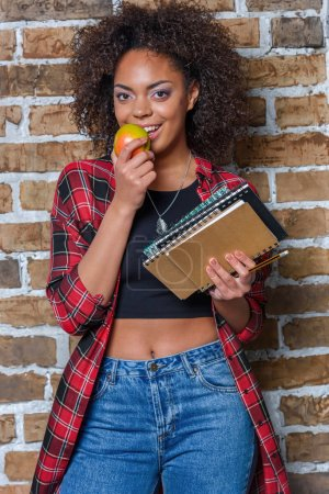 african american girl eating apple and holding notebooks while looking at camera