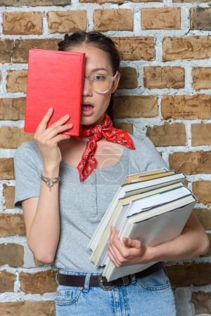 stilvolle asiatische Mädchen mit Büchern mit Gesichtsausdruck