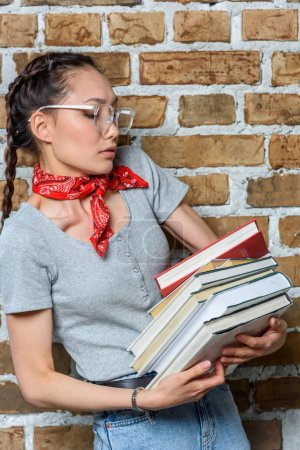 portrait of young asian student in glasses holding books