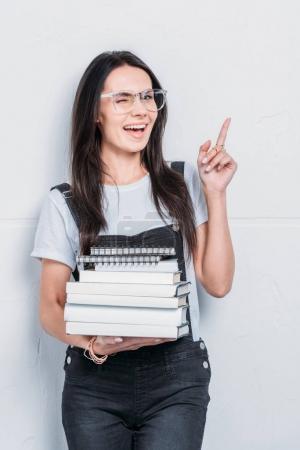 Photo pour Jeune étudiant caucasien tenant des livres et pointant du doigt - image libre de droit
