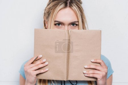 young blonde woman holding book in front of face and looking at camera