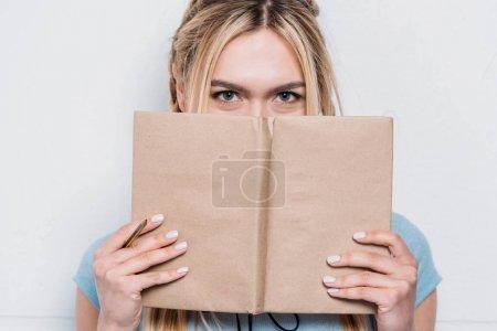 Photo pour Jeune femme blonde tenant livre devant le visage et regardant la caméra - image libre de droit