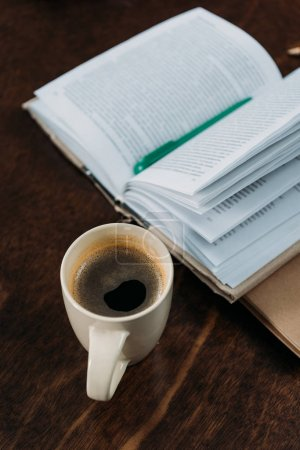 close up of coffee cup with book and pen on wooden tabletop