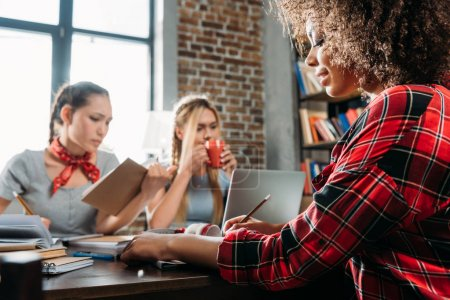 young multiethnic women working while sitting at table in home office