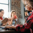 Young multiethnic women working while sitting at t...