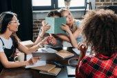 """Постер, картина, фотообои """"Многонациональные девушки, работающие, сидя за столом в домашнем офисе"""""""