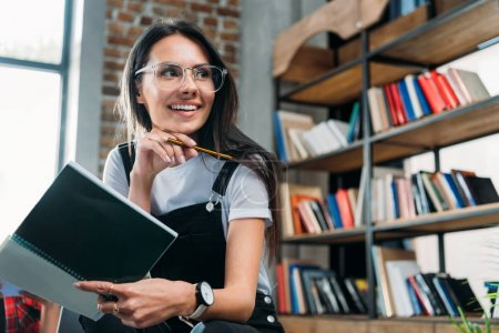 young smiling caucasian woman holding notebook and looking away at library