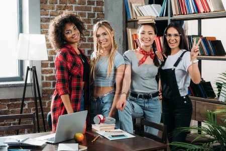 Photo for Young stylish multiethnic women posing together at home library - Royalty Free Image