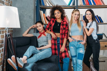 young stylish multiethnic women posing together at home library