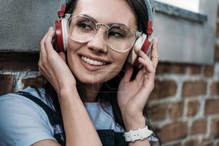 Close-up portrait of smiling young woman in eyeglasses wearing headphones and looking away