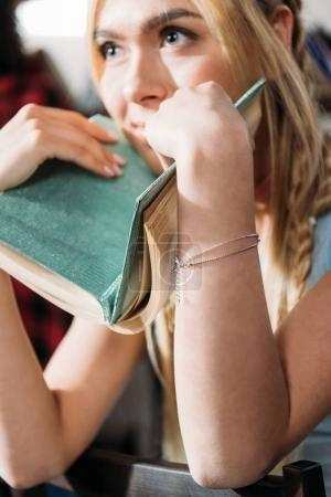 Close up portrait of caucasian girl holding book and looking away