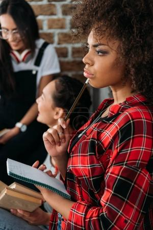 Photo for African american girl holding notebook in thoughtful pose while her friends talking - Royalty Free Image