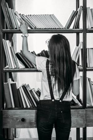 Black and white photo of young woman standing near bookshelves and choosing books