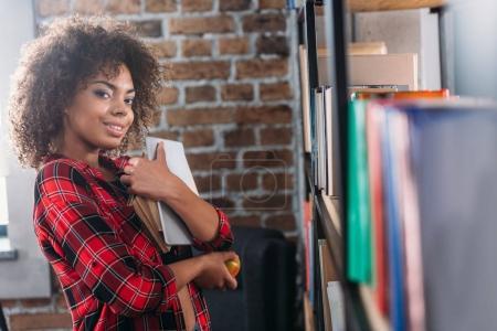 Photo pour Attrayant jeune étudiant afro-américain tenant des livres et souriant à la caméra - image libre de droit