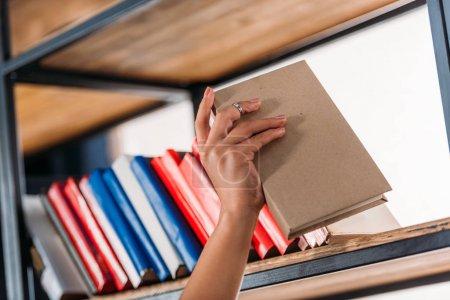 Photo pour Plan recadré d'un étudiant tenant un livre à la bibliothèque - image libre de droit