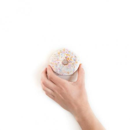 Cropped shot of person holding fresh tasty donut isolated on white