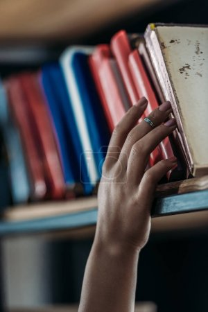 Cropped shot of student holding book at bookshelf in library