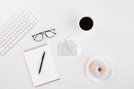 Top view of blank notebook with pen, eyeglasses, keyboard, computer mouse, cup of coffee and tasty doughnut at workplace