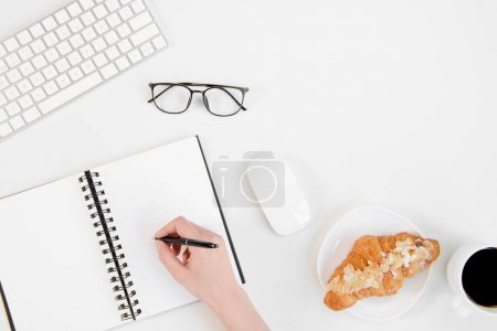 Top view of person writing in notebook with pen, eyeglasses, keyboard and coffee cup with croissant at workplace