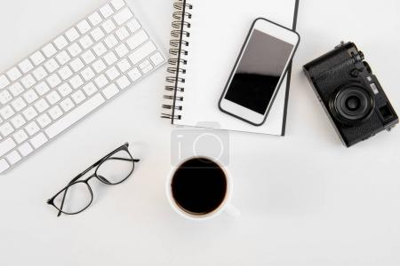 Photo for Top view of cup of coffee, keyboard, notebook, eyeglasses, smartphone and camera at workplace - Royalty Free Image