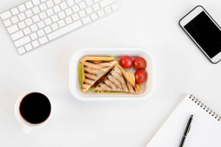 Top view of sandwiches with tomatoes in lunch box, notebook with pen, cup of coffee, smartphone and keyboard at workplace